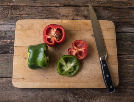 paprica: red and green bell paprica with knife and cutting board on a wooden table? Stock Photo