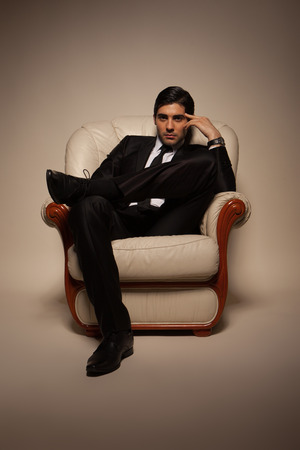 manhood: Confident successful young handsome man businessman in elegant suit with tie on armchair . Manhood. Male Beauty. Fashion model studio shoot . Italian Style Stock Photo