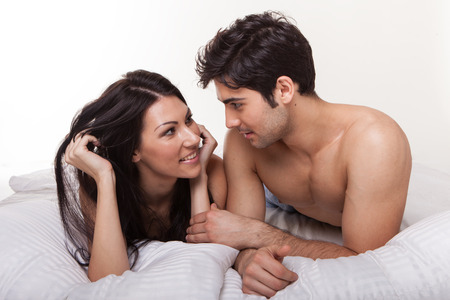 having sex: Overhead close up portrait of a young romantic couple hugging and kissing, laying down on a white bed, having sex and loving each other. Love and relationships lifestyle, interior bedroom.