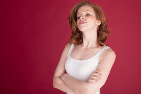 freckles: serious woman with freckles on red with blue eyes with her hands crossed. Stock Photo