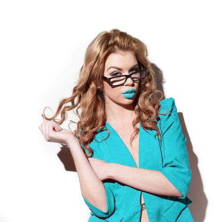 secretaria sexy: secretaria atractiva en la chaqueta azul que juega con su pelo rizado de color rojo Foto de archivo