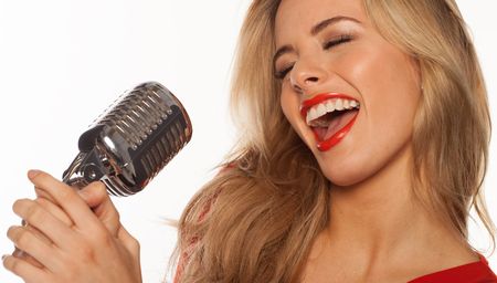 sexy blonde singer singing to retro microphone on white photo