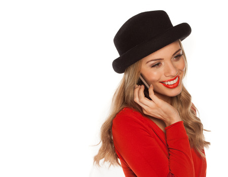 Young happy attractive female in red dress using her mobile phone, shoot over white background photo