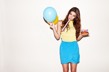 ballons: pretty birthday girl with ballons and cake blowing the trumpet
