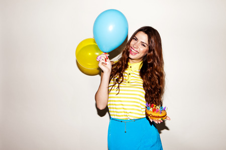 happy brunette woman celebreting her birthday with the cake and ballons Foto de archivo