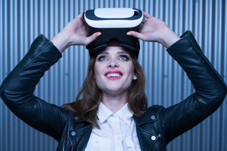 carpark: happy beauty woman getting experience using VR-headset glasses of virtual reality in the carpark Stock Photo