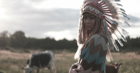 Beautiful ethnic american indian lady with roach on her head and cows in the background