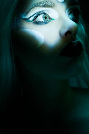 mesmerising: mesmerising eye of woman in dark scene portrait with frozen makeup  looking up Stock Photo