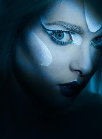 in vouge: mesmerising eye of woman in dark scene portrait with frozen makeup  looking up Stock Photo