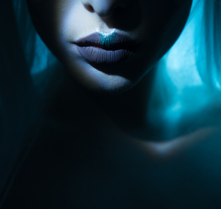 kisses: beauty lips with atmospheric light effect comming out of the dark , blue lips with grey