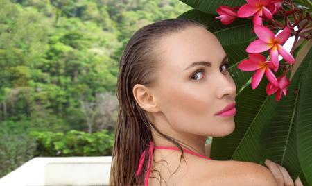 maillot de bain fille: Gros plan de jeune femme sexy bikini porter avec les cheveux mouillés et la fleur d'arbre au toit sur une journée ensoleillée