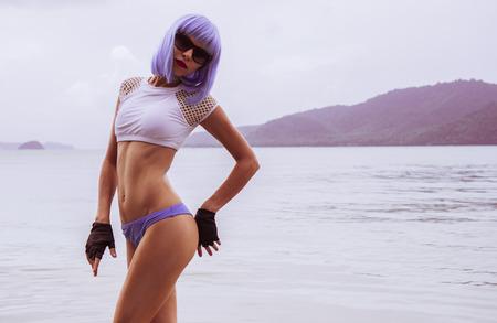 fingerless gloves: Sexy beautiful woman in modern futuristic style posing in the sea. Creative look of woman wearing bikini, blue wig, black leather fingerless gloves in the water