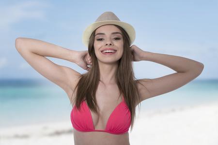femme brune sexy: Sourire belle brune sexy en bikini rose et un chapeau sur la plage sur la mer et le fond de ciel