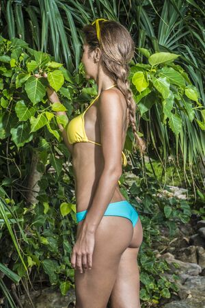 Beautiful happy young girl in a sexy bikini by the green tropical plants