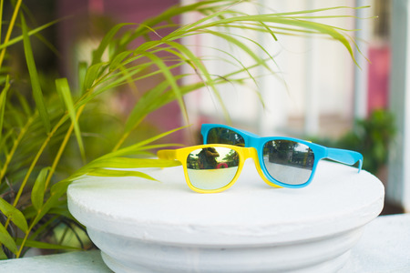 dyke: Yellow and blue sunglasses on white terrace dyke over blurred pink house background