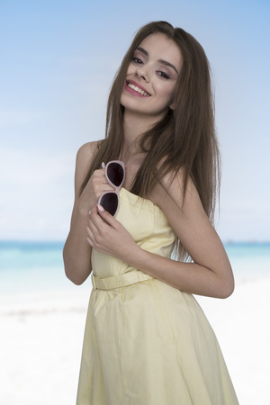 feeling happy: Young and happy woman in yellow dress posing with a sunglasses in the hand on the beach. Feeling free and joyful
