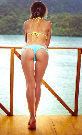 skinny girl: Sexy  female body wearing bikini by the beach. Girl with a perfect shape resting on a summer vacation