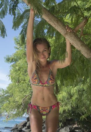 maillot de bain fille: Jolie femme blonde en maillot de bain coloré souriant et debout sur un brach d'arbre vert sur une belle journée d'été