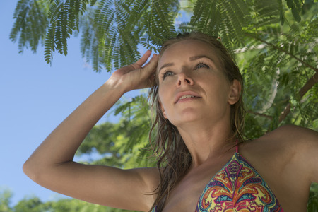 colourful sky: Closeup of pretty blonde woman wearing colourful swimwear on a beautiful summer day over tree and sky background Stock Photo