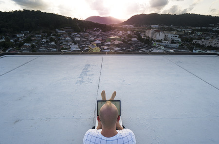 Top view of young man back holding laptop computer on his knees while sitting on a rooftop over beautiful sunset and city landscape backgorund. Freelance and technology Stock Photo
