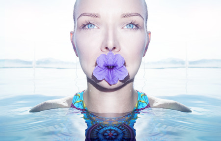 pretty eyes: Face closeup of pretty blonde woman with beautiful blue eyes and purple flower in her mouth looking at camera in infinity rooftop swimming pool on a sunny day over sky background