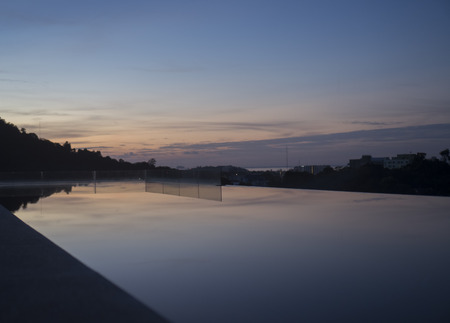 city of sunrise: Silhouette of Phuket city during sunrise view from infinity pool Stock Photo