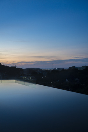 developing: Silhouette of Phuket city during sunrise view from infinity pool Stock Photo