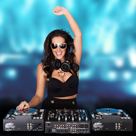 disc jockey: Jubilant sexy female disc jockey standing behind her mixing deck laughing and holding up her hand against a backdrop of blue party lights with copyspace