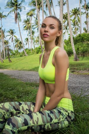 Young pretty blonde happy female wearing exercise clothing sitting on the grass in tropical palm trees garden during beautiful summer day