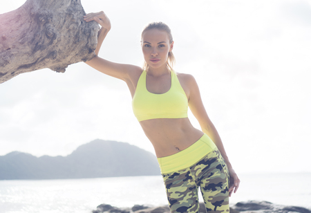 Young pretty blonde female wearing exercise clothing standing on tropical beach near the sea
