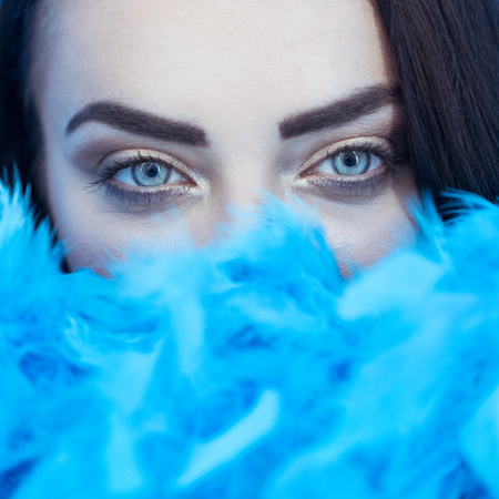 feather boa: Closeup portrait of beautiful seductive brunette woman smiling and looking into the camera while playing with blue feather boa over blue wall background