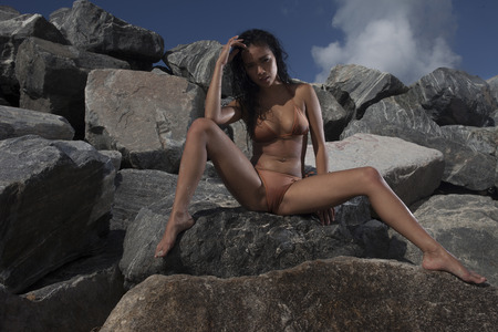 Bottom view of sexy young asian woman wearing brown bikini with wet hair sitting on the rock during sunny summer day over blue sky and rocky background
