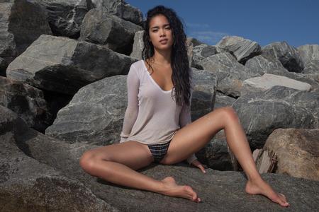 traje de baño: Vista inferior de la mujer asiática joven atractiva que desgasta parte inferior del bikini y ver thgrouh camiseta blanca con el pelo mojado que se sienta en la roca durante el día soleado de verano sobre el cielo azul y el fondo rocoso