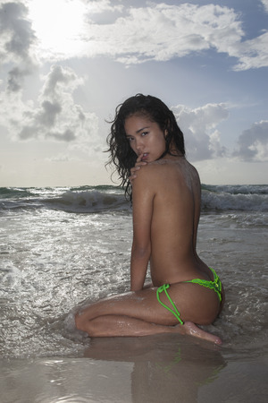 nude outdoors: Sexy young asian topless woman wearing green bikini bottom with wet hair sitting in the water and looking into the camera during sunny summer day over sea and sky background