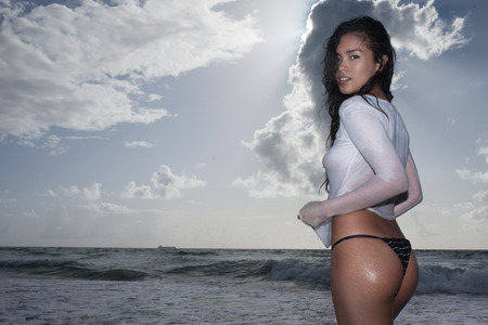 Side view of sexy young asian woman wearing bikini bottom and see through white t-shirt with wet hair standing in the water and looking into the camera during sunny summer day over sea and sky background