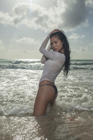 bikini bottom: Sexy young asian woman wearing bikini bottom and see through white t-shirt with wet hair standing in the water and looking into the camera during sunny summer day over sea and sky background