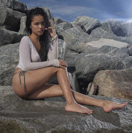 Sexy young asian woman wearing bikini bottom and see thgrouh white t-shirt with wet hair sitting on the rock during sunny summer day over blue sky and rocky background