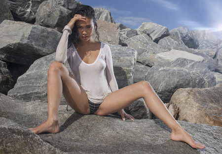 bikini bottom: Sexy young asian woman wearing bikini bottom and see thgrouh white t-shirt with wet hair sitting on the rock during sunny summer day over blue sky and rocky background