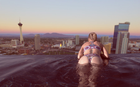 Back view of blonde woman enjoying the city view of Las Vegas at sunset from infinity pool