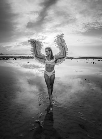 romantic sky: Black and white photo of romantic young beauty as an angel on the beach. Blonde pretty female woman wearing pink wings, feather bra and bikini bottom standing in the sea over cloudy sky background Stock Photo