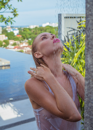 mujer bañandose: Front view of sexy blonde woman in bikini and white see-through tank top taking outdoors shower on the rooftop surrounded with tropical garden