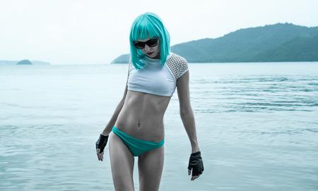 sexy female: Sexy beautiful woman in modern futuristic style posing in the sea. Creative look of woman wearing bikini, blue wig, black leather fingerless gloves in the water