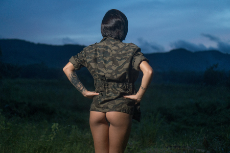 Back view of sexy girl wearing military style jacket and black underwear isolated on green field over beautiful sunset
