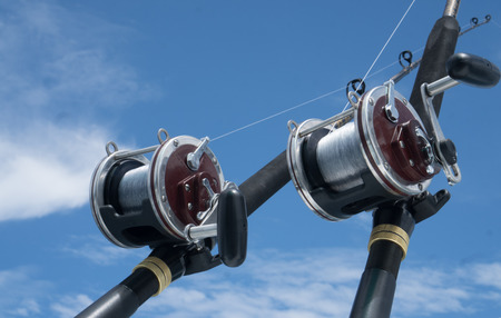 fishing rig: Fishing rods on a boat over blue sky. Picture of two fishing rods in pole holders on the back of a boat