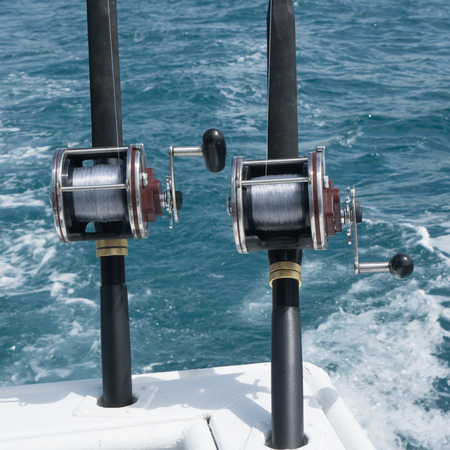 fishing rig: Fishing rods on a boat over blue sea. Picture of two fishing rods in pole holders on the back of a boat Stock Photo