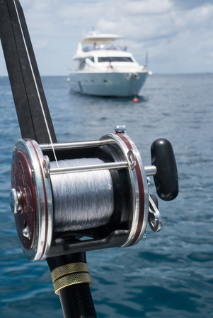 fishing rig: Fishing rod on a boat over blue sky and white sailing boat in the sea. Picture of fishing rod in pole holders on the back of a boat