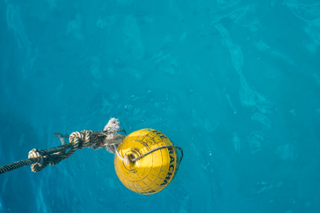 mooring: Yellow mooring buoy in the sea, mark-point coral reef zone beside the boat