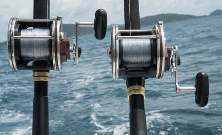 fishing rig: Fishing rods on a boat over blue sea and sky. Picture of two fishing rods in pole holders on the back of a boat