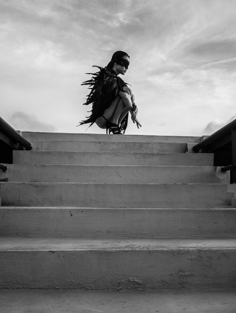 fondo blanco y negro: foto en blanco y negro de la mujer hermosa ángel seductora con los ojos cubiertos usan la ropa interior y correas de cuero que se agacha en el techo sobre el cielo nublado