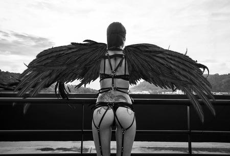 Volver ver foto en blanco y negro de la mujer hermosa ángel seductora con los ojos cubiertos usan la ropa interior y las correas de cuero de pie en el techo sobre el cielo nublado